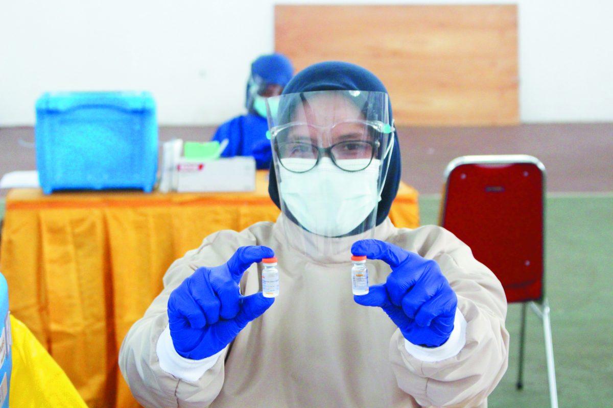 Seorang petugas medis menunjukkan botol dosis vaksin Covid-19 sebelum memberikannya kepada tenaga kesehatan di Gedung JK Arenatorium Unhas, Senin (15/2) Foto : Ainun Afiah/IDENTITAS